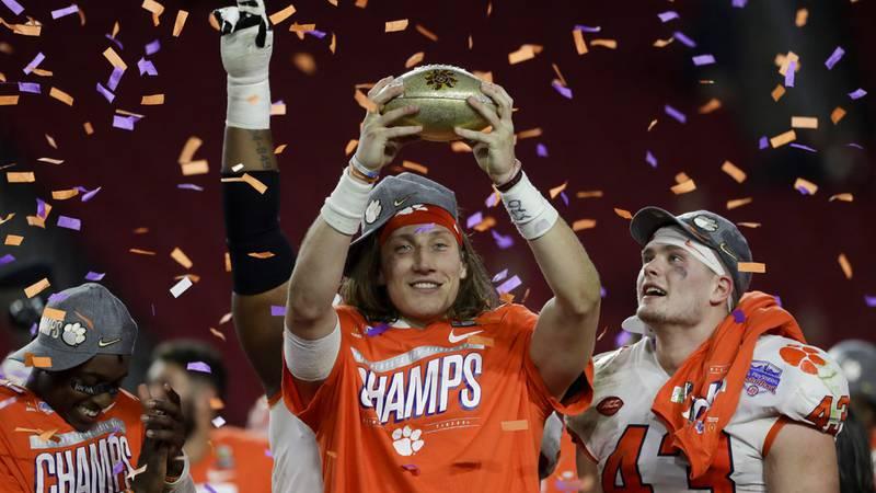 Clemson quarterback Trevor Lawrence holds up the trophy after Clemson's 29-23 win over Ohio...