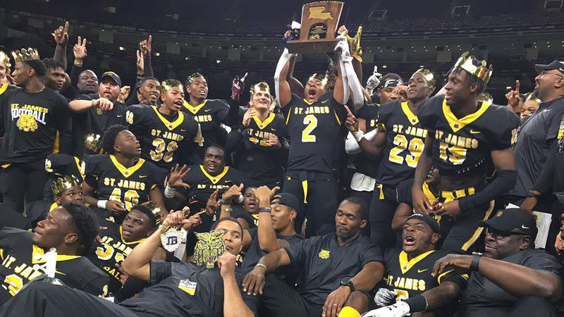St. James running back Sean Lebeouf is surrounded by teammates and coaches as he hoists the...