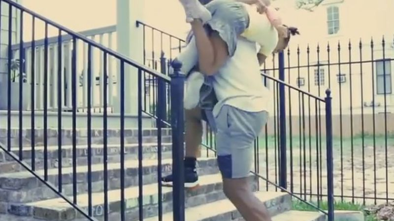 Saints safety Malcolm Jenkins lunges up and down the stairs with his daughters draped over his...