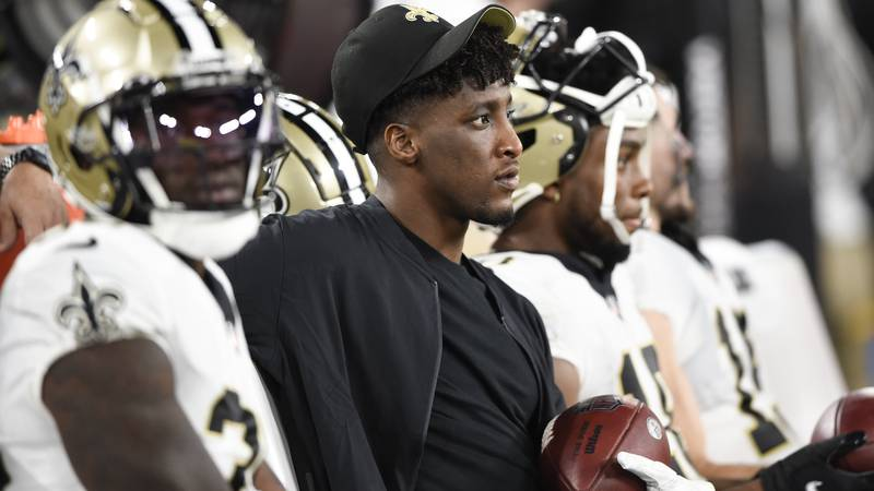 New Orleans Saints wide receiver Michael Thomas, center, sits on the bench with teammates...