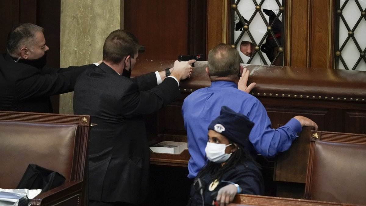 Police with guns drawn watch as protesters try to break into the House Chamber at the U.S....