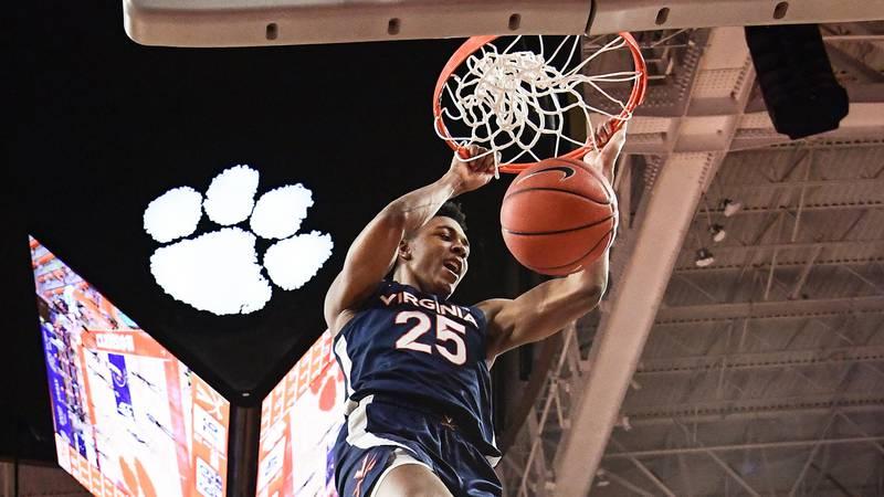 Virginia guard Trey Murphy III(25) hangs on the rim after dunking near Clemson senior forward...
