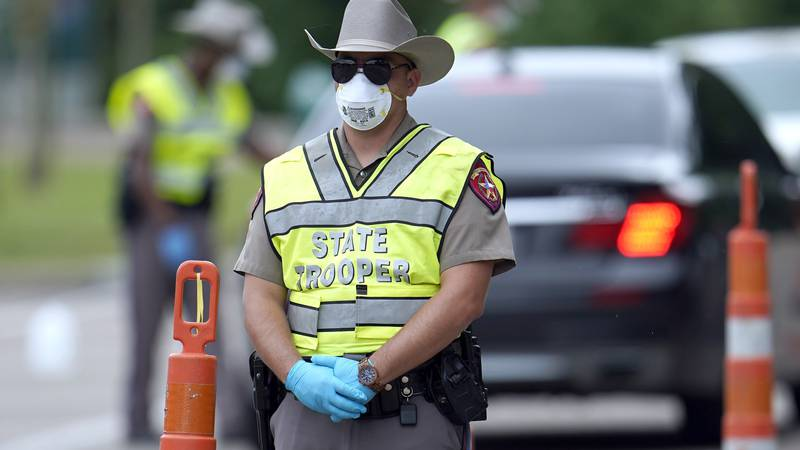 A Texas Department of Public Safety State Trooper waits to check motorists at a checkpoint in...