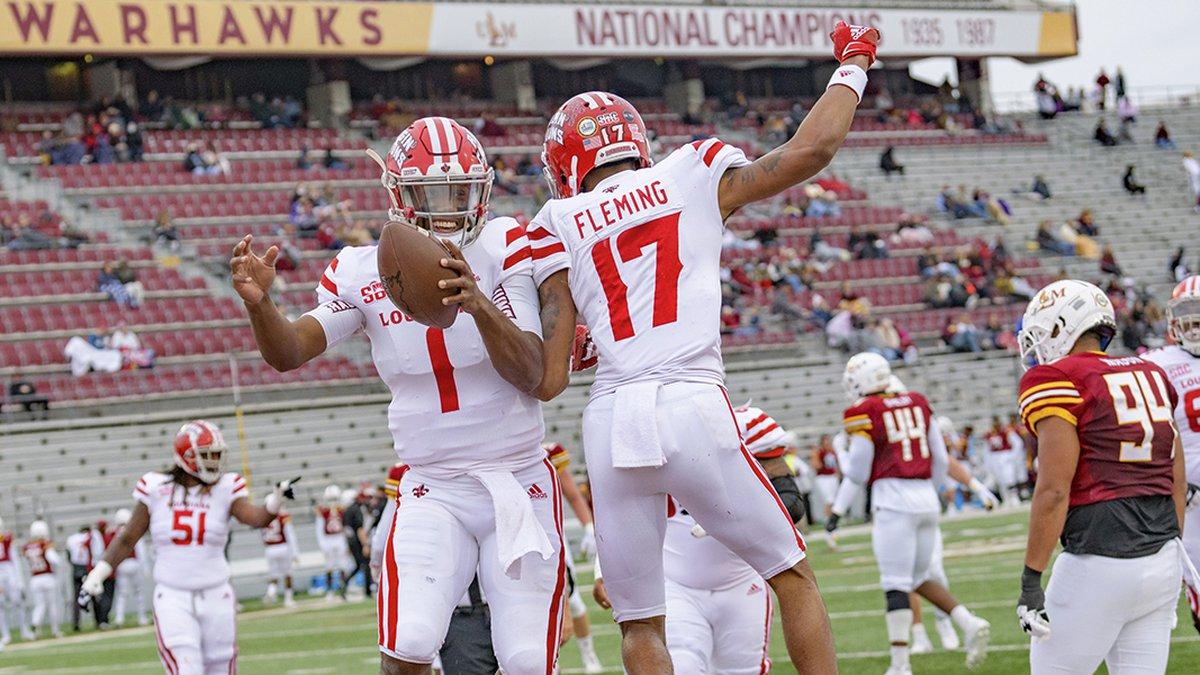 Louisiana-Lafayette quarterback Levi Lewis (1) celebrates a touchdown with wide receiver Dontae...