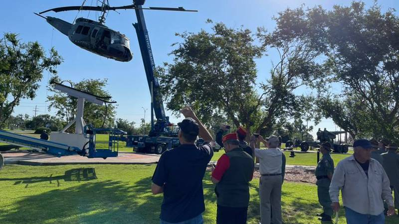 A Huey helicopter from the Vietnam War, damaged by the hurricanes, is removed.