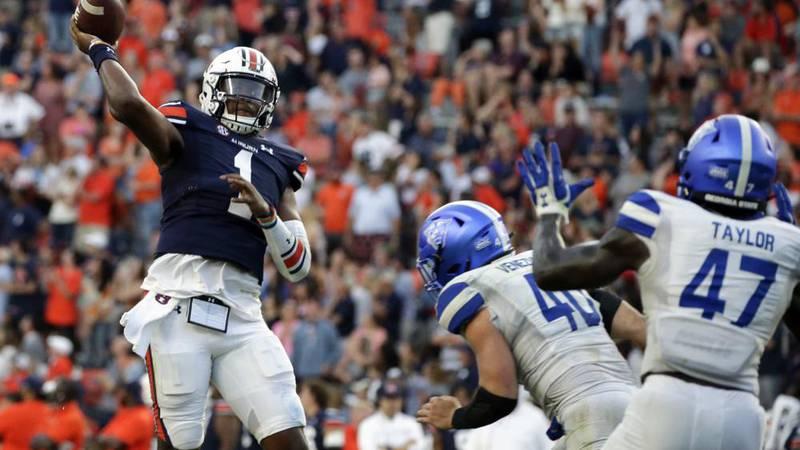Auburn quarterback TJ Finley (1) throws a pass for a touchdown to take the lead over Georgia...