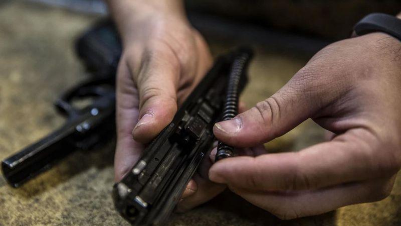 Cpl. Chris Sagan conducts a maintenance check on a Beretta M9 pistol at III Marine...