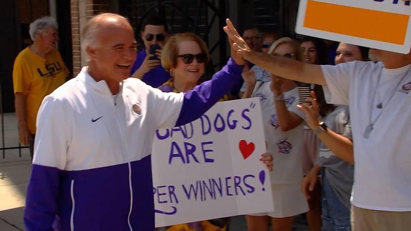 LSU head coach Paul Mainieri high-fives a fan as the Tigers leave campus on Thursday, June 10,...